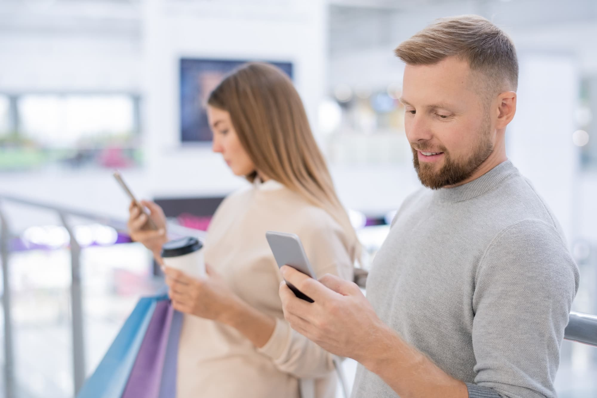 Young man and his girlfriend with smartphones scrolling through online offers